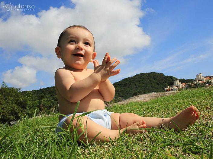Bebê na grama com céu azul